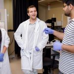 three students in lab coats chatting