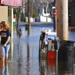 view of a flooded street corner with two people