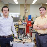 dr. shen and dr. sazzonov in a lab filled with electrical equipment