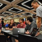 Students with laptops sit in the ferg ballroom