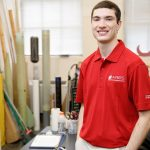 Peyton Strickland in a red shirt in a workshop with lots of rocketry items