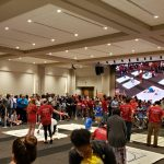Young students work with UA students and faculty in a large room filled with people
