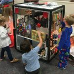 children play with a box that has all sorts of lights and buttons and knobs