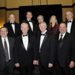 9 people in formal wear stand together indoors for the State Engineering Hall of Fame