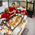 Four people in red shirts work on a robot in a lab