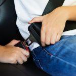 hands buckling up a seat belt