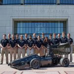 Crimson Racing team stands outside football stadium with their race car