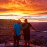 two men outside on a mountain top at sunset