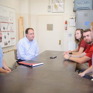 Students, faculty and alumni talk around a table in a lab.