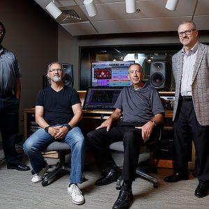 Three men sit in on-campus recording studio