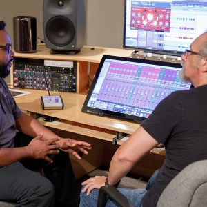 Two men sit at table with recording equipment