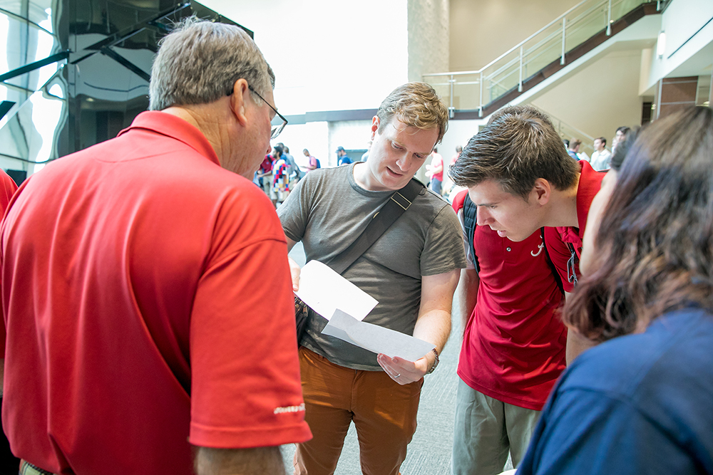 Four people look at two sheets of paper in the Ferg common area