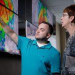 Two people looking at a hurricane model on screens
