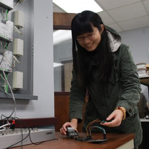 A student works with wireless board in a lab on campus