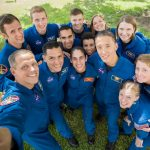 13 people in astronaut flight suits pose for a group selfie style shot