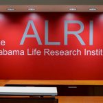 Red wall with ALRI the alabama life research institute printed on it