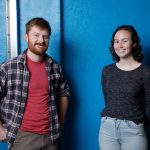 Two engineering students (man and woman) with a blue wall behind them