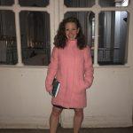 Student in pink coat standing in front of doors