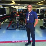 artis brown stands in front of people working on a race car