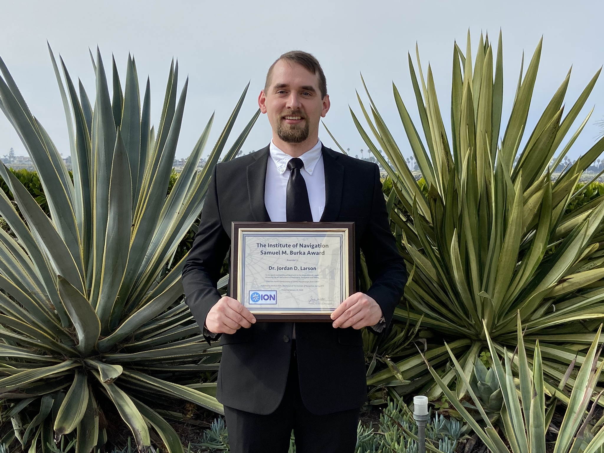 A man holds a plaque award in front of southwestern vegetation