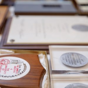 Many award and honor plaques laid out across a table