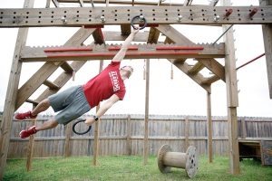 A man swings on a wooden practice obstacle course in his back yard