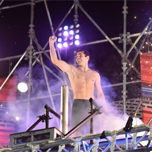 Shirtless guy stands on platform with purple lights behind him