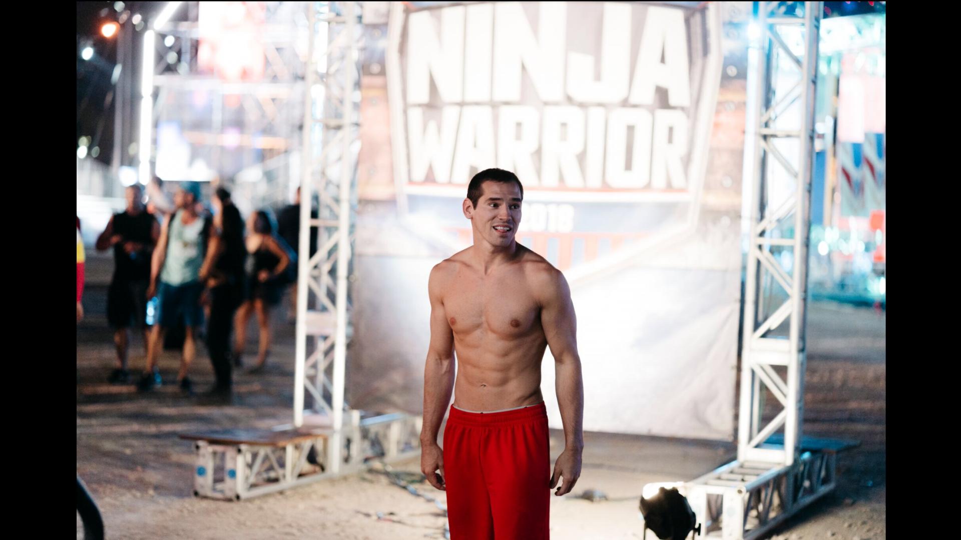 Casey Suchocki stands on platform with Ninja Warrior sign