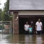 A family stands in their garage amid flood waters up to their knees
