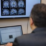 A man looks at brain scan images