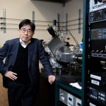 Dr. Hong stands in lab next to machinery