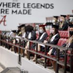 Graduates sit in the stands wearing masks at commencement