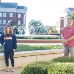 Dr. Gray and student stand on the engineering quad with the fountain in background