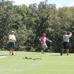Four people on golf course on a sunny day