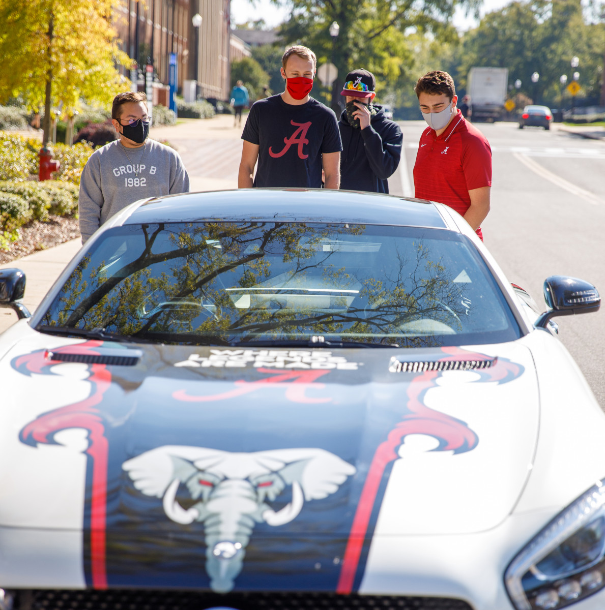 4 people outside looking at a UA themed race car