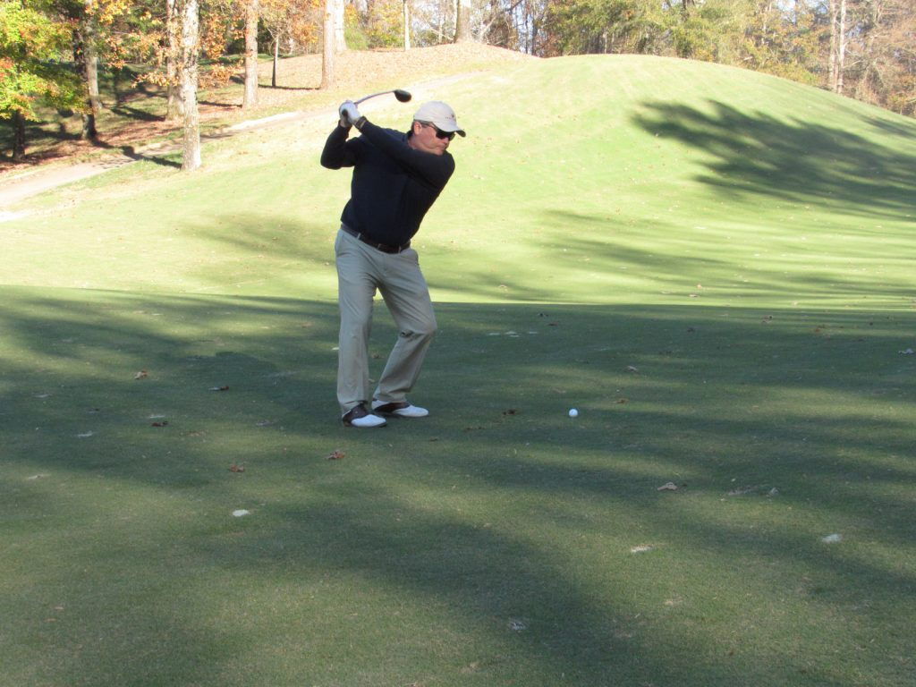 Golfer in black shirt and white cap taking a swing on the green