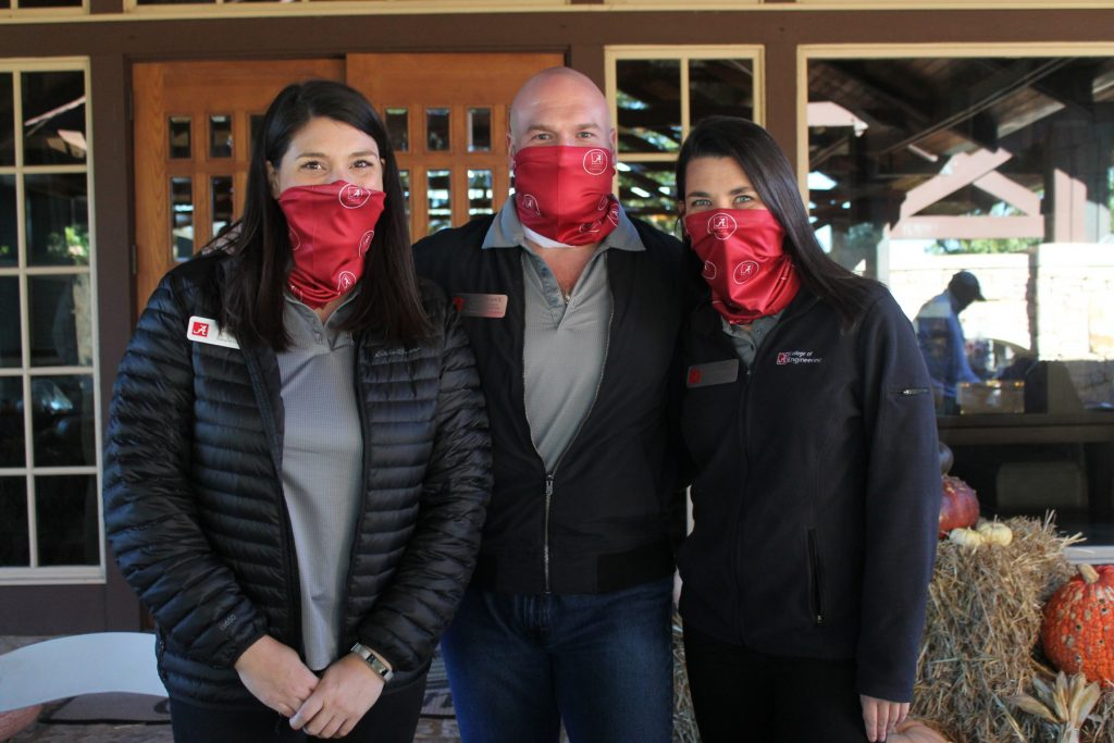 two women and a man, all in red masks, pose for a picture