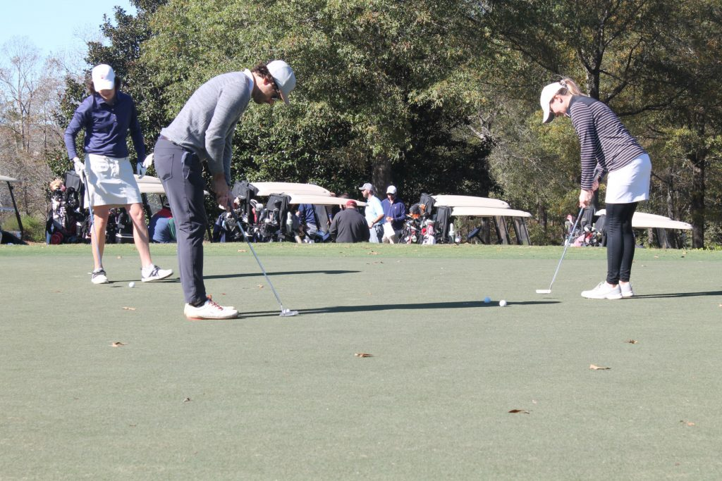 a single golfer in grey with a white hat putting with golf carts and people in background