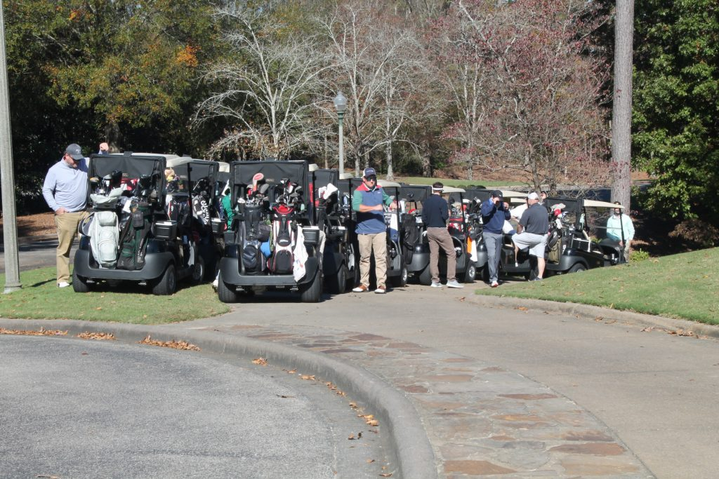 lots of golfers and their golf carts