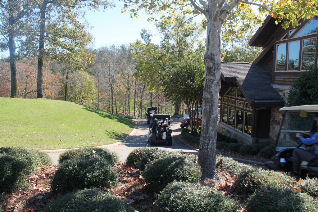 golf carts driving past the club house