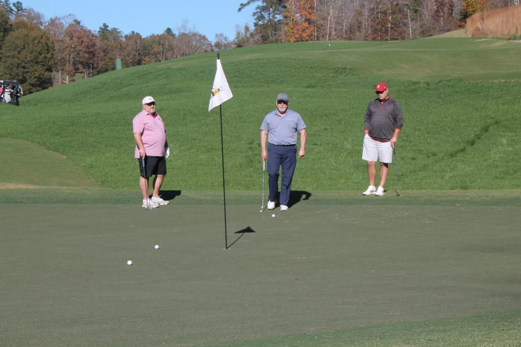 three golfers, one in a pink shirt and the others in shades of blue-grey, stand next to a hole with a flag