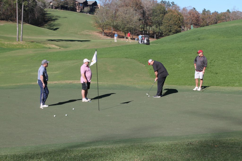 Four golfers gathered around a hole with flag still in it