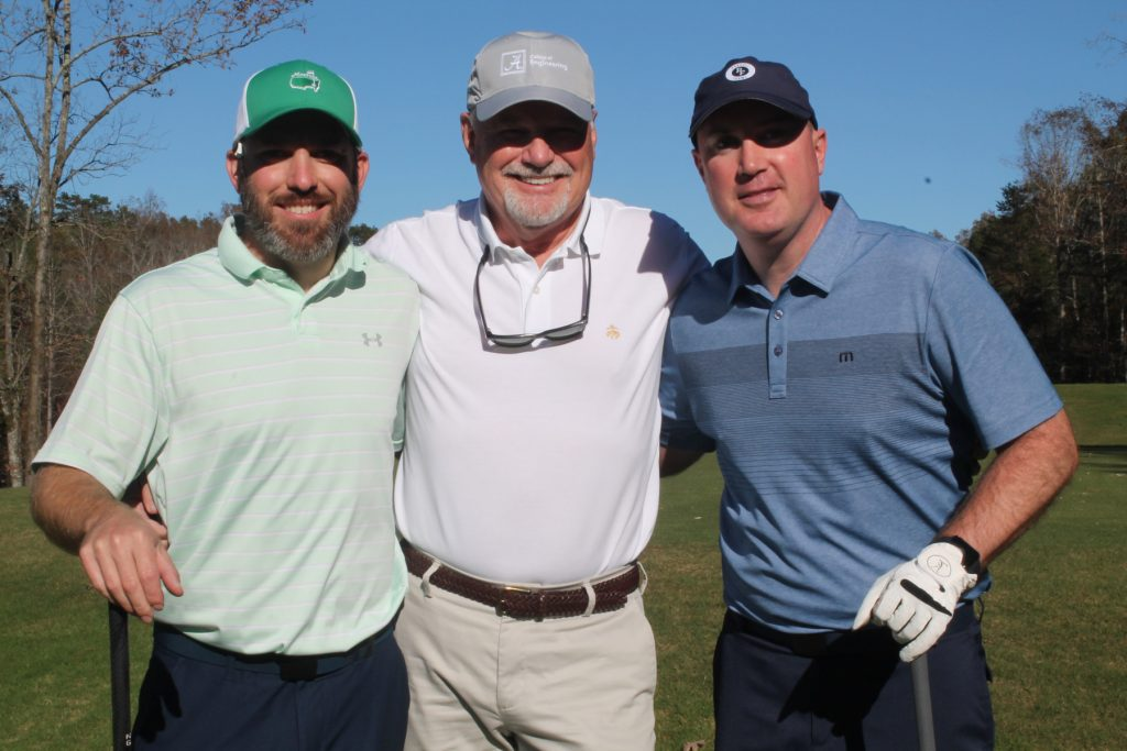 3 golfers, one in a green hat and mint shirt, pose for a picture