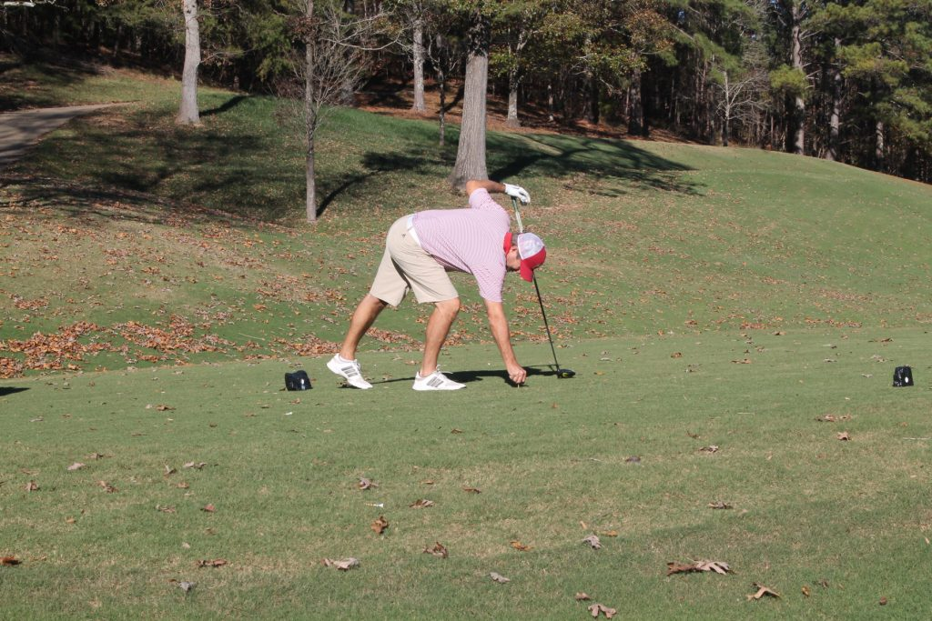 A golfer leans down to position his ball on the green