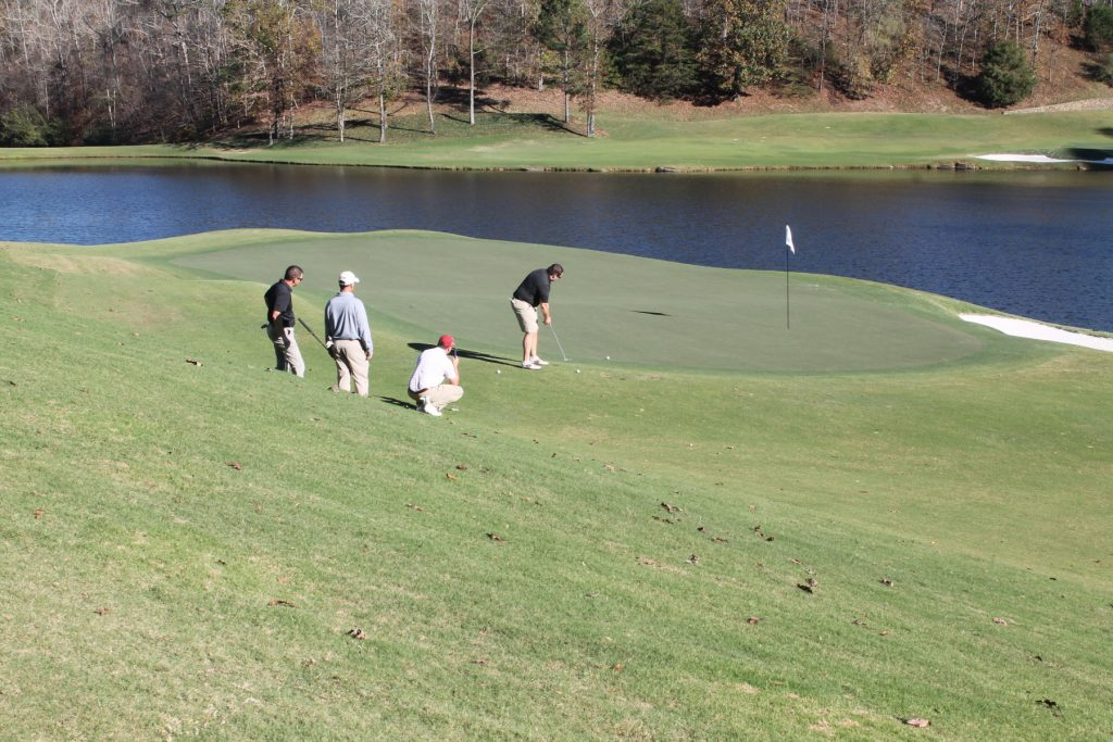 Three golfers watch the fourth in a black shirt about to hit the ball