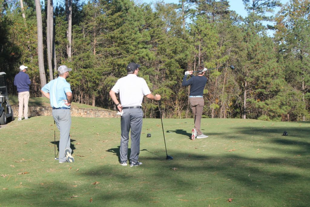4 golfers,. one leaning on his club, wait for the next drive