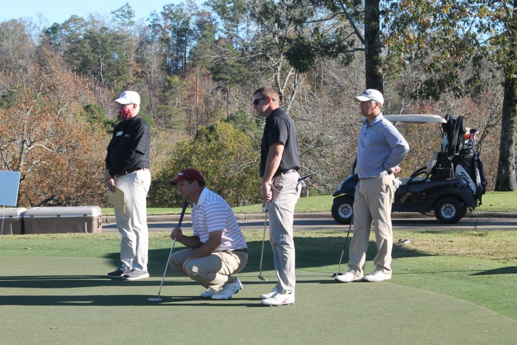 4 golfers, one squatting, with a golf cart in the background