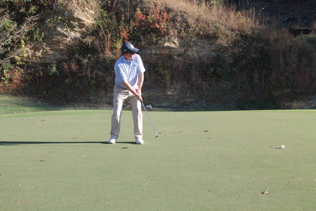 A golfer in a black cap hits the ball