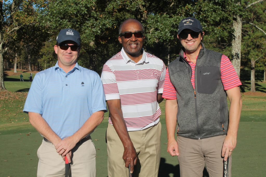 3 golfers, one in a pink and white striped shirt, pose for a photo