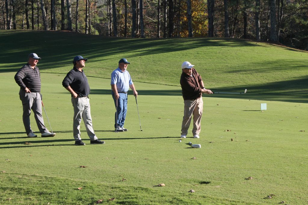3 golfers watch a fourth in brown shirt judge his swing